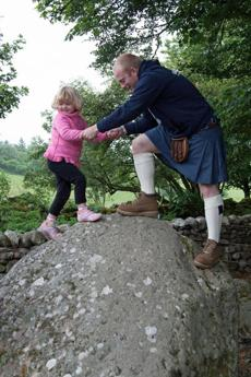 Charlotte Levesque and Gordon Pearson scale a boulder at Clava Cairns, a prehistoric burial site near Inverness.